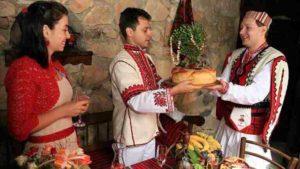 Кум дает жениху свадебный хлеб.